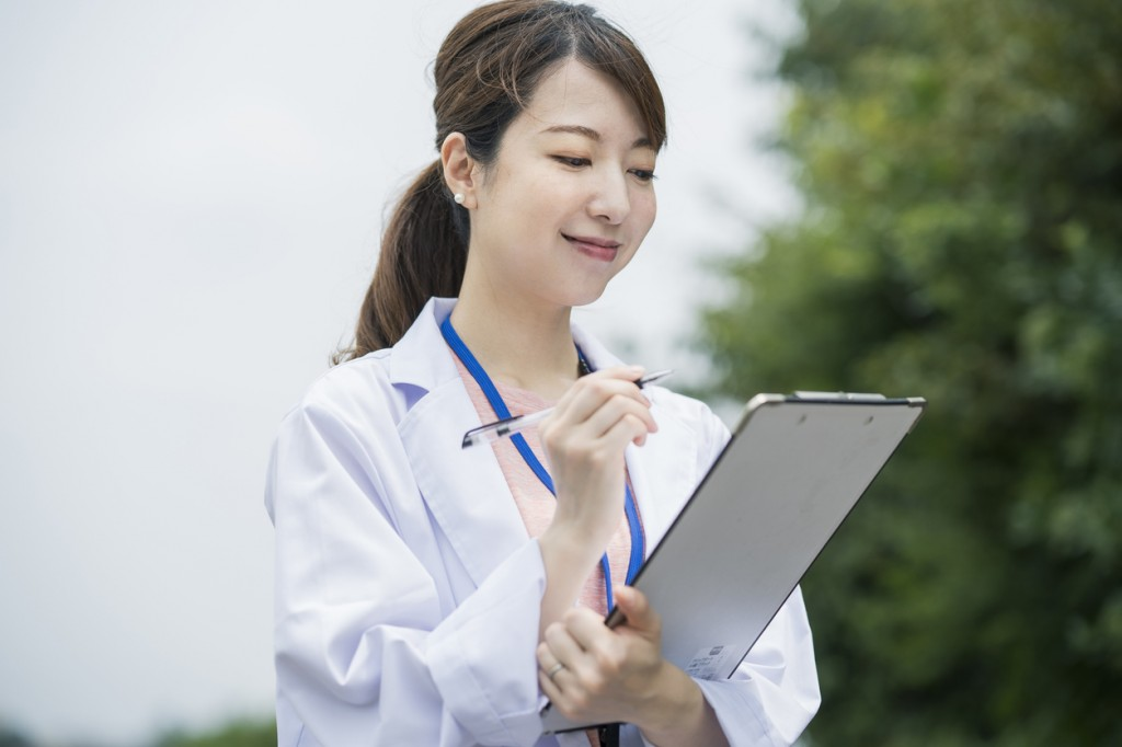 Asian female medical worker with medical chart and pen